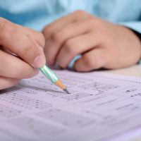 close up of someone's hands filling in a scantron for an exam